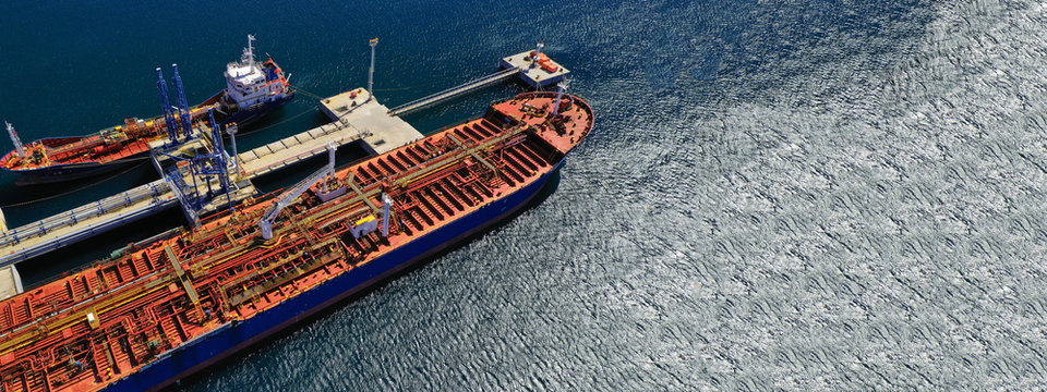 Aerial drone ultra wide top down photo of industrial LPG gas tanker ship cruising in low speed near Asian industrial plant