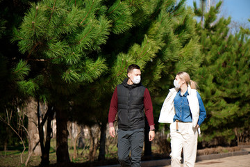Young European man and woman in protective disposable medical mask walking outdoors afraid of dangerous NCoV 2019 influenza coronavirus mutated and spreading in China Fotomurales
