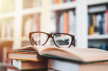 Glasses on stack of books. Library in the background. Books and glasses.