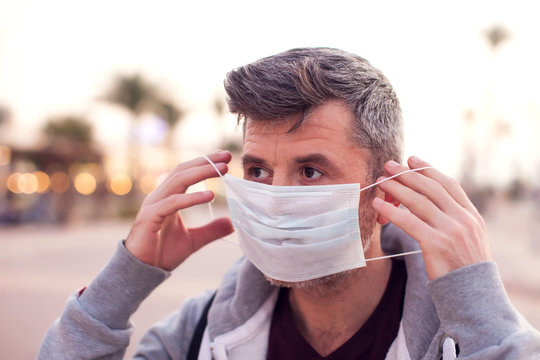 A portrait of man with medical face mask outdoor. People, medicine and healthcare concept
