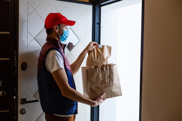 Papiers peints Magasin alimentation Delivery man holding paper bag with food on white background, food delivery man in protective mask