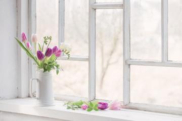 beautiful tulips on old white windowsill