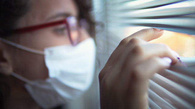 Corona Virus Quarantine Isolation. Sick woman of corona virus looking through the window and wearing mask protection and recovery from the illness in hom