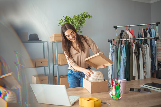 Woman working at home, selling items online. Online shopping makes happy a lot of people. Woman packing item that she sells online. Items that I send has to be perfect