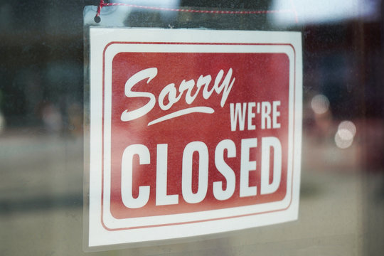 Sorry we're closed sign behind dirty glass door during corona lockdown