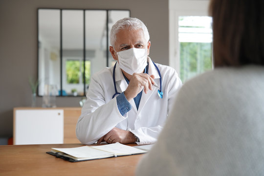 Doctor meeting with patient, wearing protection mask