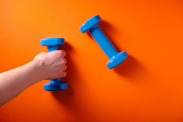 Girl takes a blue dumbbell in hand, on an orange background