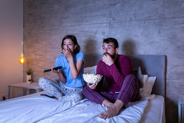 Couple watching horror movie in bed Wall mural