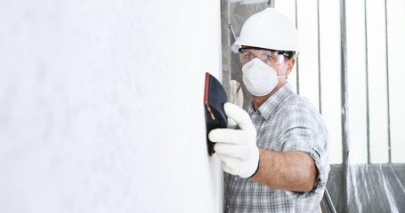 man sand the wall with sandpaper, professional construction worker with mask, safety hard hat, gloves and protective glasses. interior building site, copy space background