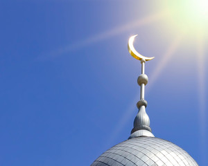 Mosque of Muslim. Crescent on copper covered dome and minaret of mosque against blue sky. Symbol of Islam and Ramadan.