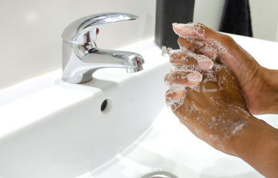 Black woman conscientiously washing her hands with soap. Selective focus on hands. Disinfection. Hygiene concept.