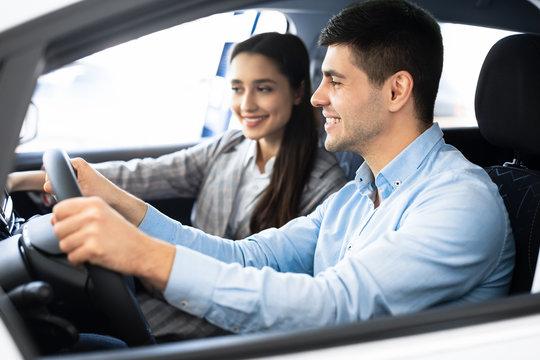 Wife And Husband Choosing Car In Dealership Shop