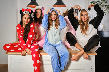Charming women dressed up in plush pajamas in form of cartoons characters are having fun at bachelorette party, posing on a kitchen table. Close-up.
