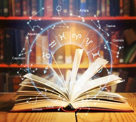 Wall Mural - Old open book on a bookshelf background with astrology concept