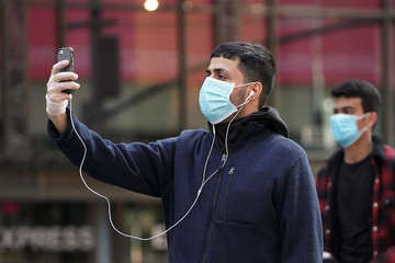 A man takes pictures as he wears a protective face mask at Times Square following the outbreak of Coronavirus (COVID-19), in the Manhattan borough of New York City