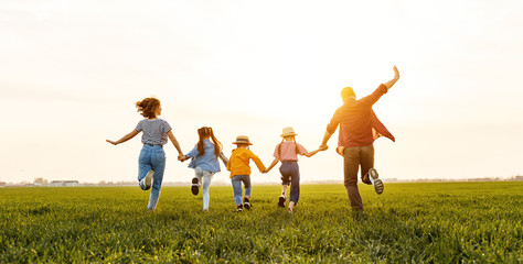 Anonymous happy family running back in field in summer evening
