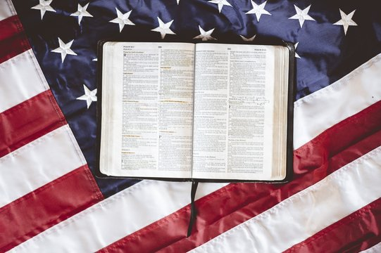 Closeup shot of the Bible open in pages put on the American flag - perfect for praying concept