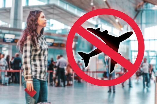 A woman stands at the airport, waiting for the departure of the plane.Blurred.Prohibition sign. Close up. The concept of a ban on flights, the closure of state borders and the virus pandemic