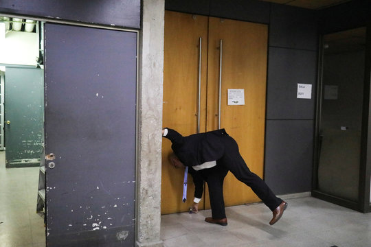"""A man closes a classroom of the Chilean """"Universidad Catolica"""" during the outbreak of coronavirus disease (COVID-19), in Santiago"""