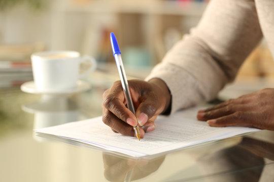 Black man hands filling out form on a desk