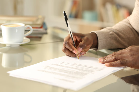 Black man hands singing contract on a desk