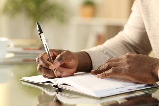 Black man hands writing reminder on agenda