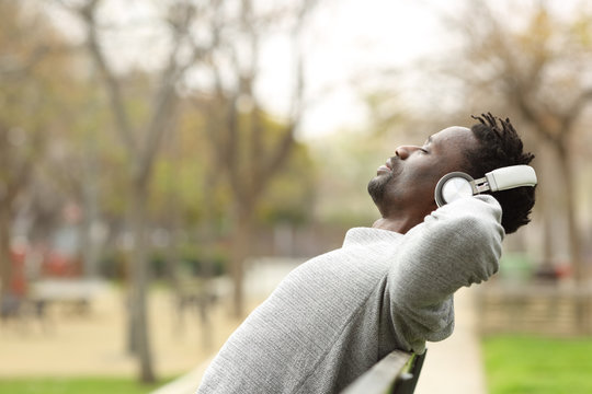 Black man relaxing on a bench listening to music