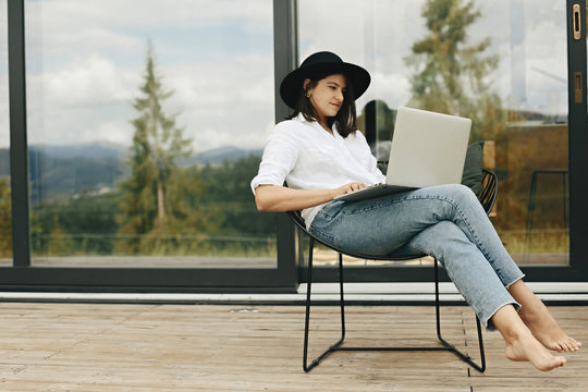 Stylish hipster girl sitting with laptop on terrace at big window. Young happy woman in hat using laptop, shopping or working online from home outdoors. Freelance and freelancer