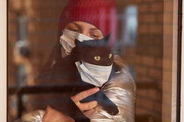 A young woman in a protective mask holds a masked cat in her arms. Conscious citizen in the fight...