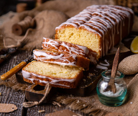 homemade rectangular sliced pound lemon cake with white glaze on top on wooden board on rustic table with sackcloth, lemon slices, vintage forks