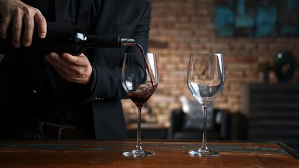 Man pouring red wine to wine glasses at home