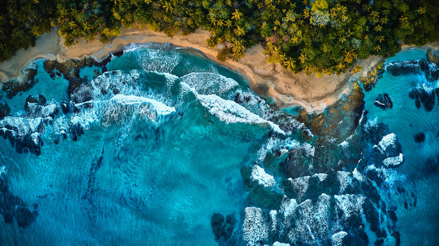 Magnificent aerial shot of a blue tropic lagoon with crystal clear water surrounded by beach and palm trees. View from the top