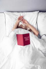 Frau mit Buch Love in the Time of Corona im Bett
