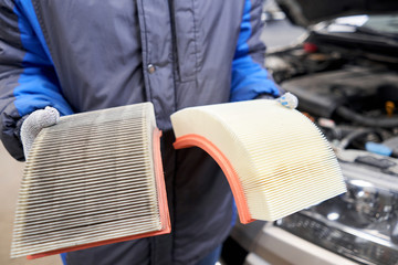 New and old dirty automotive engine air filter in the hands of an auto mechanic. Auto repair concept.