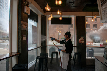 A restaurant staff member cleans the windows after closing early afternoon following the outbreak of coronavirus disease (COVID-19), in New York City