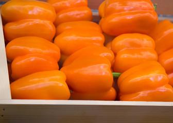 Fresh orange pepper in a wooden box