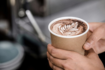 Close up shot of male hands holding take away cup of brewed hot coffee with Fern latte art design