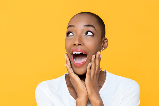 Surprised beautiful African American woman gasping and looking up aside to empty space on yellow background