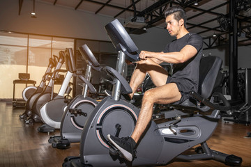 young fit men are exercising by spinning the bike in the gym. Concept of healthy with exercise. Asian young men playing exercise machines in the gym