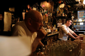 Barmen pause while serving some of the night's final drinks at McSorley's Old Ale House, which, established in 1854, is referred to as New York City's oldest Irish saloon and was ordered to close at 8:00pm as part of a city-wide order