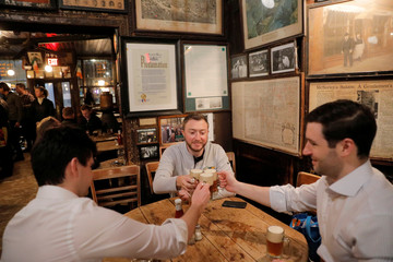 Moran Allen, Dan Anunziatta and Dan Lordan toast some of the last drinks of the night at McSorley's Old Ale House, which, established in 1854, is referred to as New York City's oldest Irish saloon and was ordered to close at 8:00pm