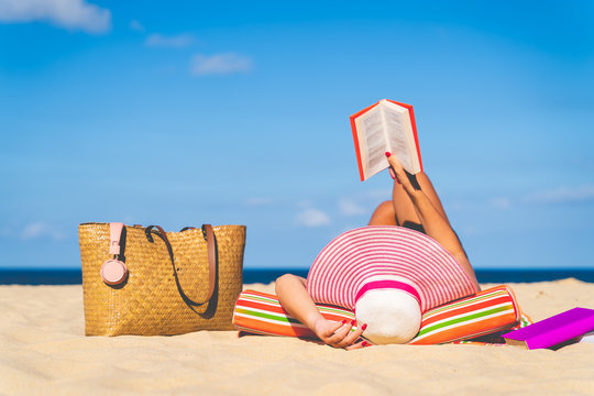 Women are sunbathing and read book on the beach there are bags and books on the side During the holidays in good weather and clear skies during summer, holidays and activities concept with copy space.