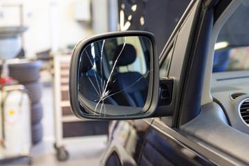 Car with a broken side mirror in a car service. Cracks in the car mirror. Insurance car body repair.