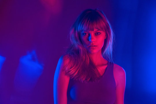Fashion attractive young blond hair 20s teenage girl model looking at camera standing at purple studio background. Pretty stylish woman in violet neon party night light concept. Portrait.