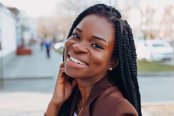 Close up portrait of a beautiful young african american woman with pigtails hairstyle in a brown business suit walks along spring streets Fotomurales