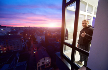 Man is standing on a balcony with panoramic windows and showing a thumb up like sign with a magical sunset outside the window. Urban landscape from height and multi-colored fiery sky with setting sun Wall mural
