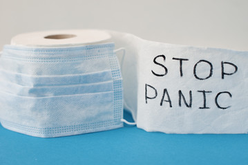 Panic buying Covid-19 Coronavirus outbreak concept. Roll of toilet paper with inscription stop panic and surgical mask on the blue background.