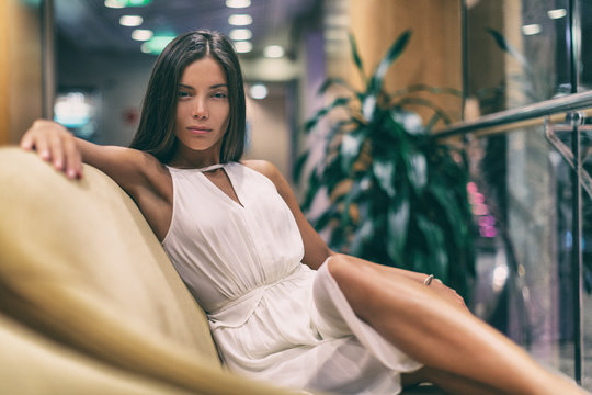 Asian fashion model posing in white dress on luxurious sofa in cruise ship. Beauty young woman high end resort.