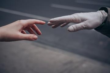 Bare hand reaching towards gloved hand