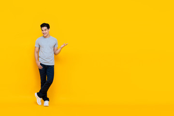 Handsome young Asian man smiling and standing with open hand gesture Fotobehang